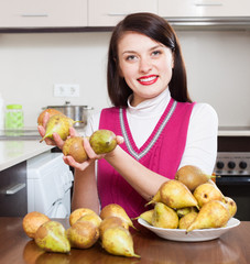 Happy young housewife with pears