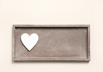 Ein weißes Herz auf rustikalem vintage Holz als Hintergrund