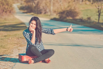 young woman sitting on a suitcase on the road hitchhiking