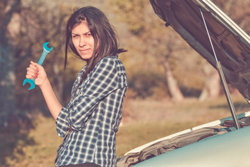 woman standing on a road with a wrench and open car hood