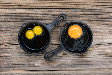 Raw eggs in pan on old wooden background