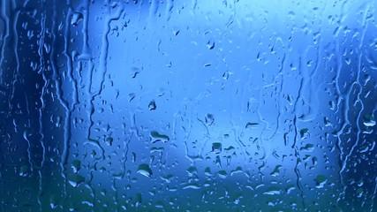 Blue color rain drops moving down a window