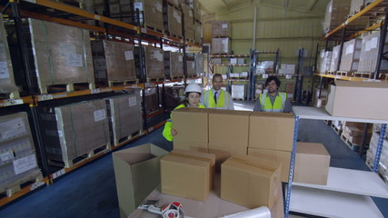 Workers in a warehouse or factory remove plain brown boxes from a pallet