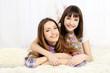 Two girls in pajamas lying