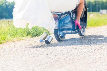 Hochzeitspaar fährt Motorroller in Hochzeitskleid und Anzug