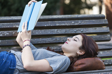 Beautiful girl lying on bench reading blue book, outdoor.