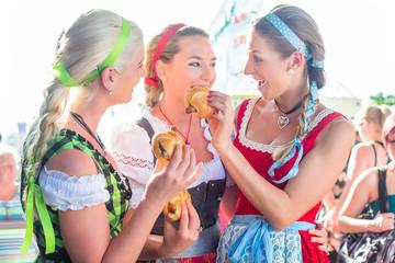 Freundinnen essen Bratwurst auf Rummel