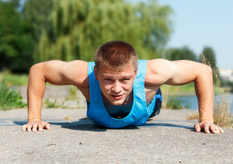 Handsome young man in good shape doing push-up while outdoor tra