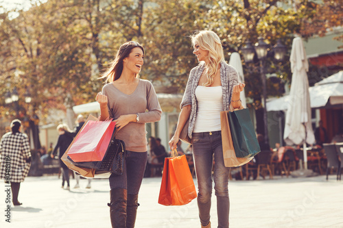 Two beautiful women walking down the street after shopping