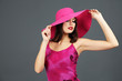 Beautiful young woman in pink dress and hat