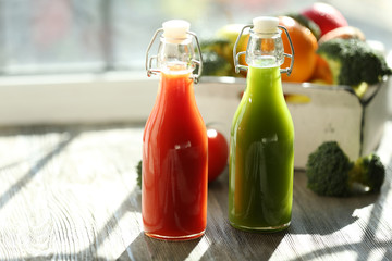 Bottles of juice with fruits and vegetables  in crate