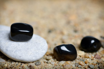 Gray and black stones in sand background