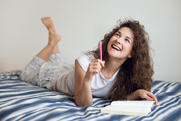 Beautiful teenage girl in bed writing notes in diary