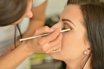 Make-up artist applying bright base color eyeshadow on model's e