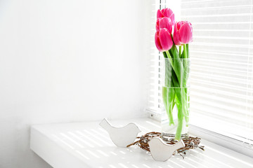 Pink beautiful tulips on windowsill with sunlight