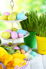 Easter eggs on vase and tulips on table on natural background