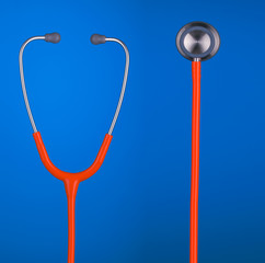 Orange stethoscope headset and bell isolated on blue background