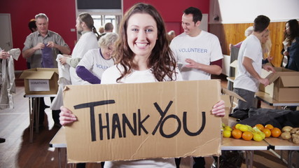 "Beautiful female charity worker holds up a ""Thank you"" sign to camera"