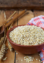Pearl barley in a ceramic bowl on a wooden background.selective