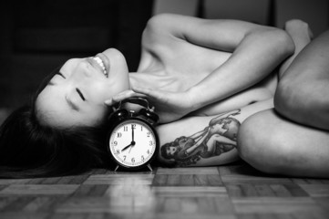 Asian woman nude lying relaxed on floor with alarm clock