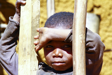 Very shy african boy with shadow on his face, poverty in Madagas