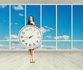 woman with clock in empty room