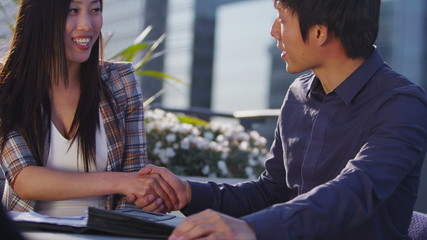 Young asian business team in open air meeting in the city shake hands on a deal