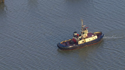 Aerial view of a tug boat traveling down London's River Thames
