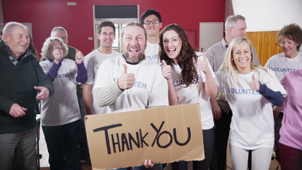 "Large group of charity volunteers smile into camera holding a ""Thank You"" sign"