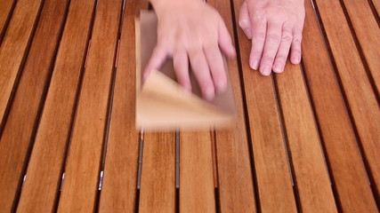 Person sanding a wooden table to prepare it for varnishing.