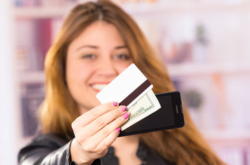 modern beautiful young woman holding cell phone, money and