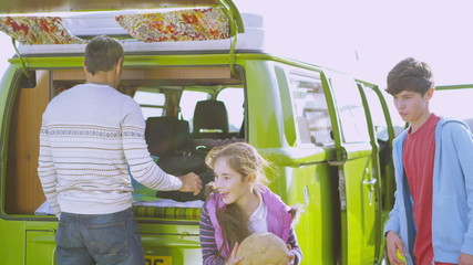 Happy family packing the camper van and going on holiday