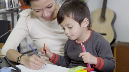 Mother and son drawing and writing with coloured pencils