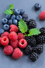 Assorted fresh berries on a black background, close-up