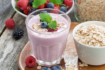 berry smoothie with oatmeal in a glass on wooden table, close-up