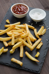 fried French fries, tomato sauce and salt on a blackboard