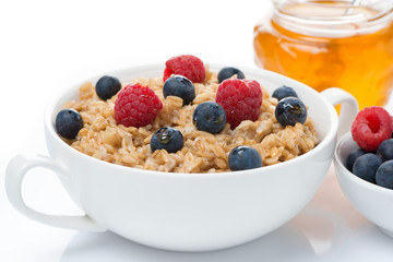 healthy breakfast - oat porridge with fresh berries and honey