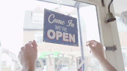 'Closed' sign is turned to 'Open' in a storefront window