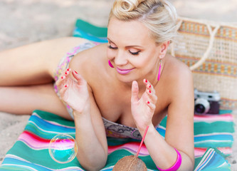 cute beautiful young woman lying on the beach with vintage color