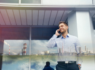 double exposure of urban businessman with phone device and indus
