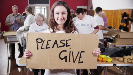 """Beautiful female charity worker holds up a """"Please Give"""" sign to camera"""