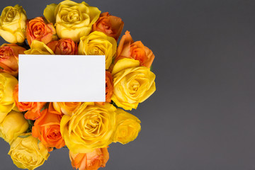 blank gift card and beautiful bouquet of orange and yellow roses
