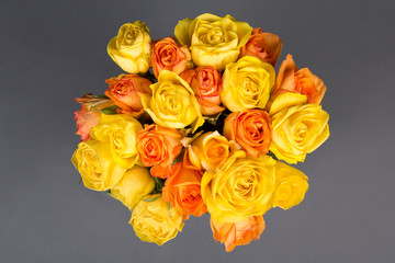 beautiful bouquet of orange and yellow roses over grey