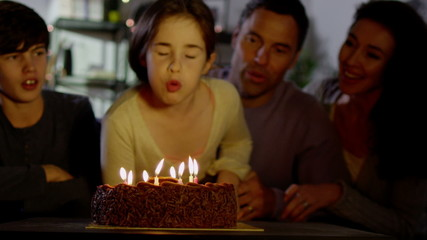 Young girl blows out the candles on her birthday cake