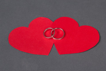 wedding rings on red heart over grey