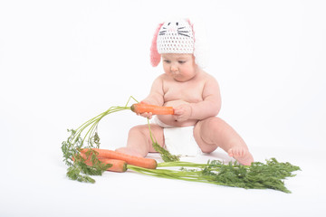 Baby boy in rabbit hat looking intently at fresh carrot in his h