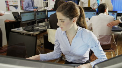 Young and ambitious female stock market trader hard at work in a busy office