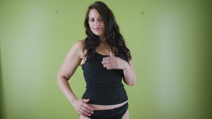 Portrait of plus size woman in underwear standing against green background