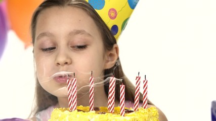 Birthday girl blows out  candles on a birthday cake. In the