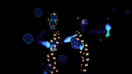 Two woman with luminous make up and bubbles